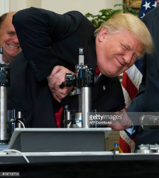US President Donald Trump uses a machine to attempt to crush a newly designed Made in America pharmaceutical glass bottle alongside Corning Chairman...