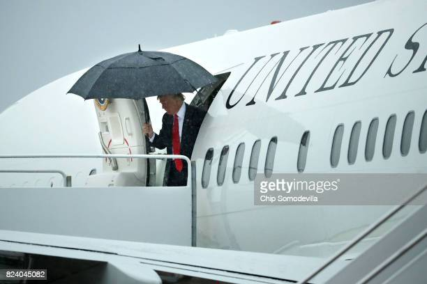 S President Donald Trump uses an umbrella while stepping out of Air Force One July 28 2017 in Joint Base Andrews Maryland Trump announced via Twitter...