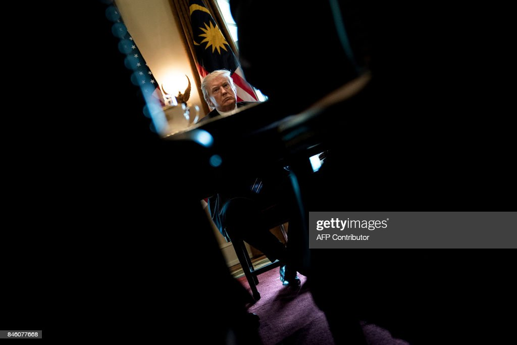 President Donald Trump waits for a meeting with Prime Minister of Malaysia Najib Razak and others in the Cabinet Room of the White House September 12, 2017 in Washington, DC. / AFP PHOTO / Brendan Smialowski