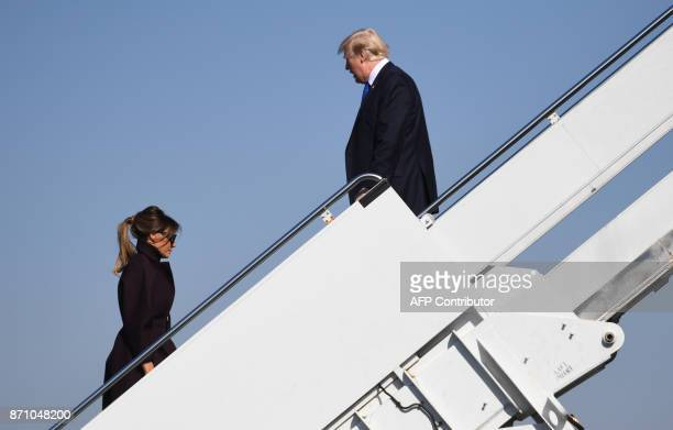 President Donald Trump waits for First Lady Melania Trump as they board Air Force One prior to departing from US Yokota Air Base in Tokyo on November...
