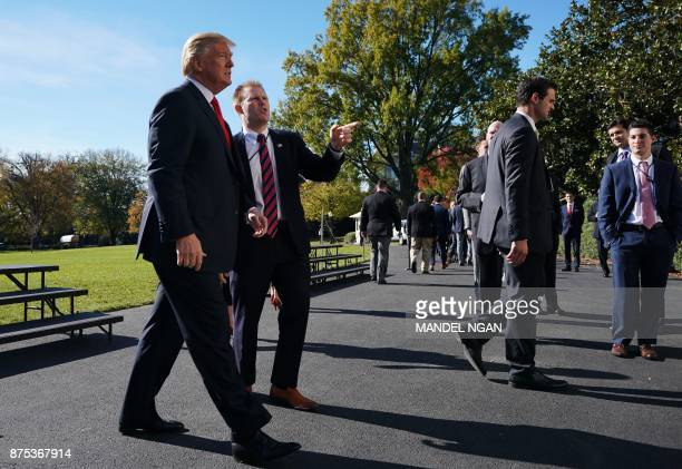 US President Donald Trump walks across the driveway during an event honoring NCAA national championship teams on November 17 2017 in Washington DC /...
