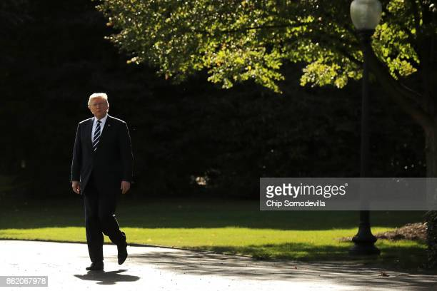 S President Donald Trump walks across the South Lawn before departing the White House on Marine One October 16 2017 in Washington DC Trump is...