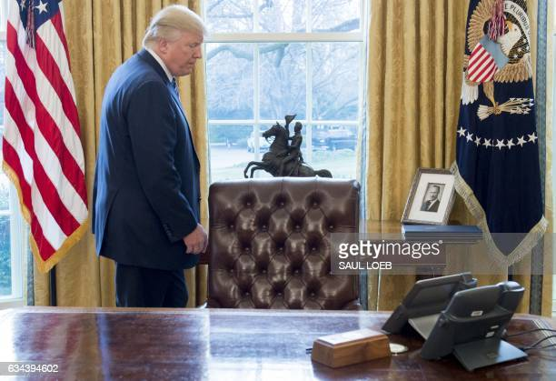 US President Donald Trump walks behind his desk after Jeff Sessions was sworn in as Attorney General in the Oval Office of the White House in...