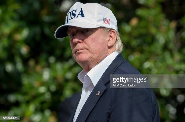 US President Donald Trump walks from Marine One upon arrival on the South Lawn of the White House in Washington DC August 27 after spending the...