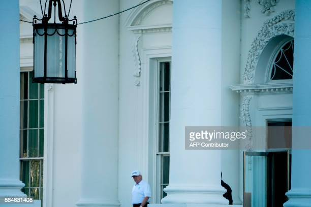 US President Donald Trump walks from the White House to his motorcade before traveling to his Virginia golf club on October 21 2017 in Washington DC...