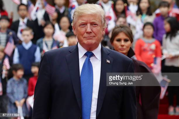 US President Donald Trump walks towards a guard of honour during a welcoming ceremony at the presidential Blue House on November 7 2017 in Seoul...
