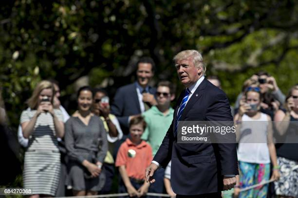 US President Donald Trump walks towards the White House past visitors on the South Lawn after arriving on Marine One in Washington DC US on Wednesday...