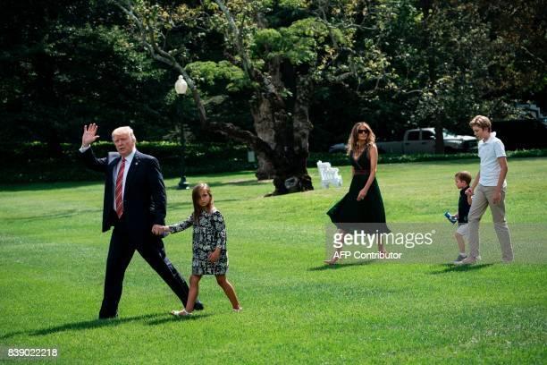 US President Donald Trump walks with granddaughter Arabella Rose Kushner US first lady Melania Trump Joseph Frederick Kushner and son Barron Trump to...