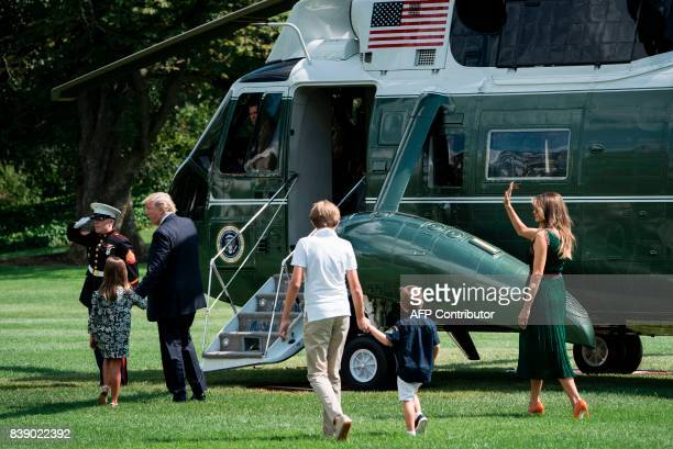 US President Donald Trump walks with granddaughter Arabella Rose Kushner son Barron Trump grandson Joseph Frederick Kushner and US first lady Melania...