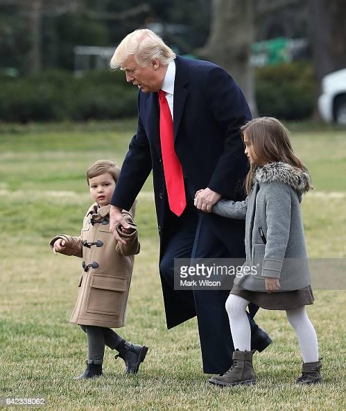 S President Donald Trump walks with his grandchildren Arabella and Joseph Kushner toward Marine One while departing from the White House on February...