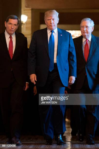 US President Donald Trump walks with Senate Majority Leader Mitch McConnell RKentucky and US Senator John Barrasso RWyoming as he arrives to speak...
