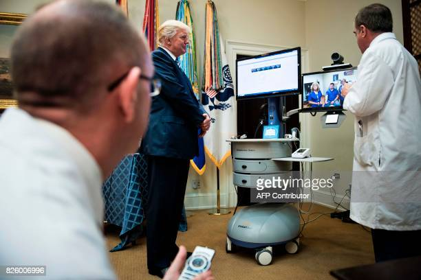 US President Donald Trump watches a teleconference with a patient after speaking about new technology used by the Department of Veterans Affairs...