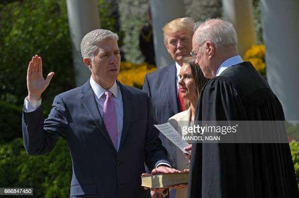 US President Donald Trump watches as Justice Anthony Kennedy administers the oath of office to Neil Gorsuch as an associate justice of the US Supreme...