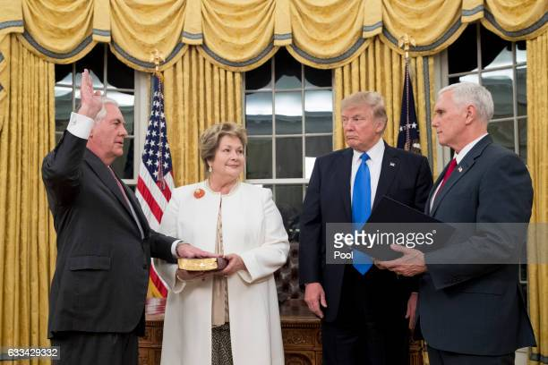 S President Donald Trump watches as Rex Tillerson accompanied by wife Renda St Clair is sworn in as the 69th secretary of state by Vice President...