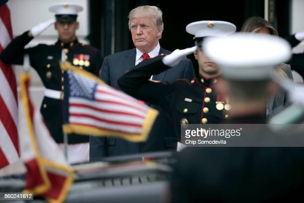 S President Donald Trump watches as the vehicle carrying Canadian Prime Minister Justin Trudeau arrives at the White House October 11 2017 in...