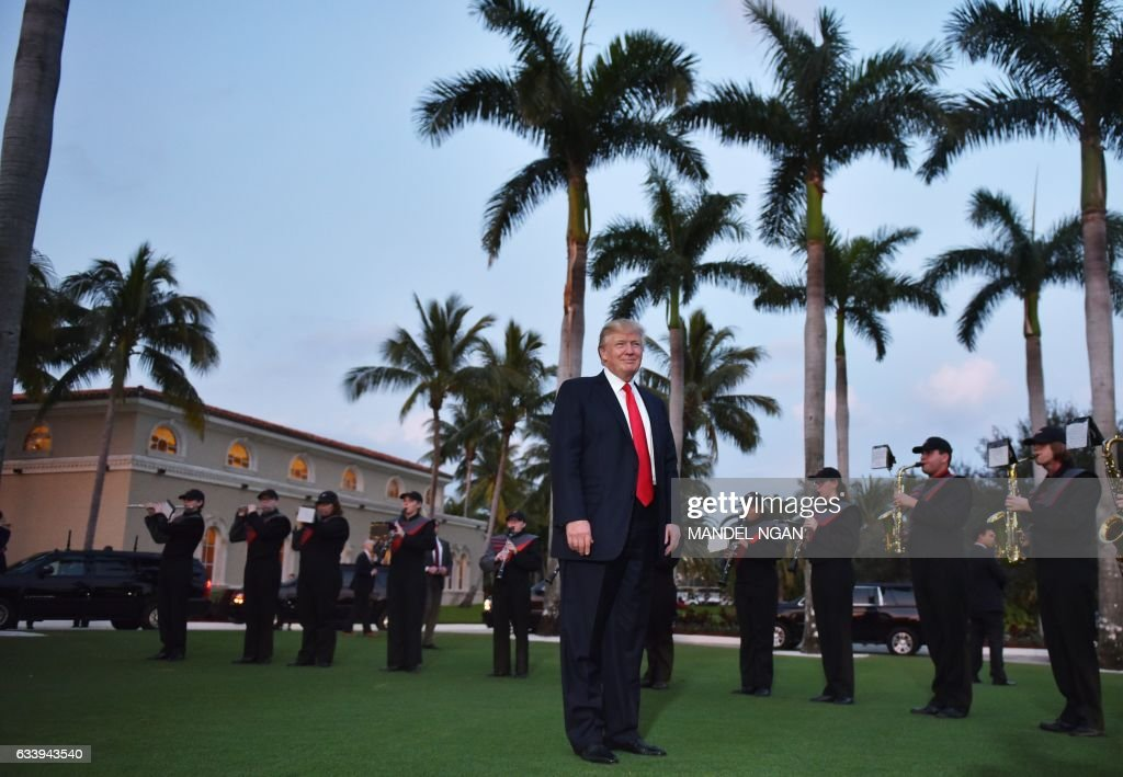US President Donald Trump watches the Palm Beach Central High School marching band which greeted him as he arrived to watch the Super Bowl at Trump International Golf Club Palm Beach in West Palm Beach, Florida on February 5, 2017. / AFP / MANDEL