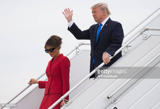 US President Donald Trump waves as he disembarks form Air Force One with First Lady Melania Trump upon arrival at Paris Orly airport on July 13...