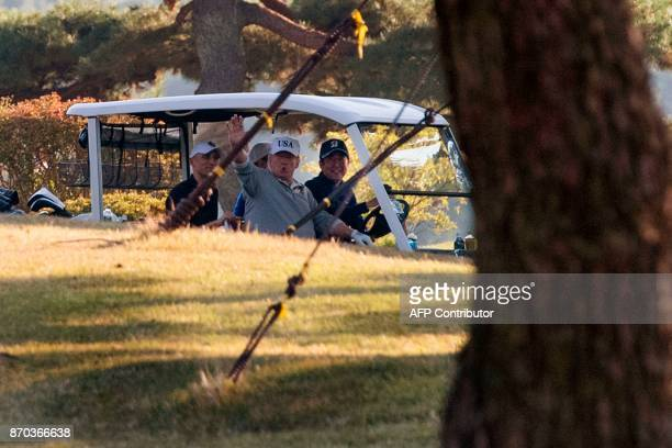 US President Donald Trump waves as he sits next to Japan's Prime Minister Shinzo Abe after playing a round of golf at the Kasumigaseki Country Club...