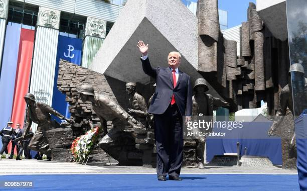US President Donald Trump waves as he stands in front of the Warsaw Uprising Monument on Krasinski Square on the sidelines of the Three Seas...