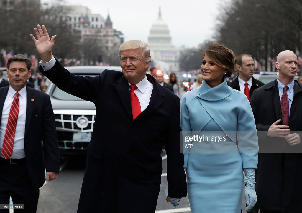 President Donald Trump waves as he walks with first lady Melania Trump during the inauguration parade on Pennsylvania Avenue in Washington, DC, on January 20, 2017 following swearing-in ceremonies on Capitol Hill earlier today. / AFP / POOL / Evan Vucci