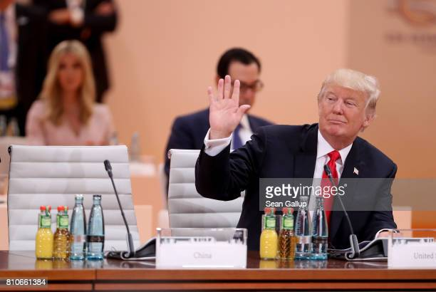 S President Donald Trump waves as Ivanka Trump and US Treasury Secretary Steven Mnuchin look on prior to the morning working session on the second...