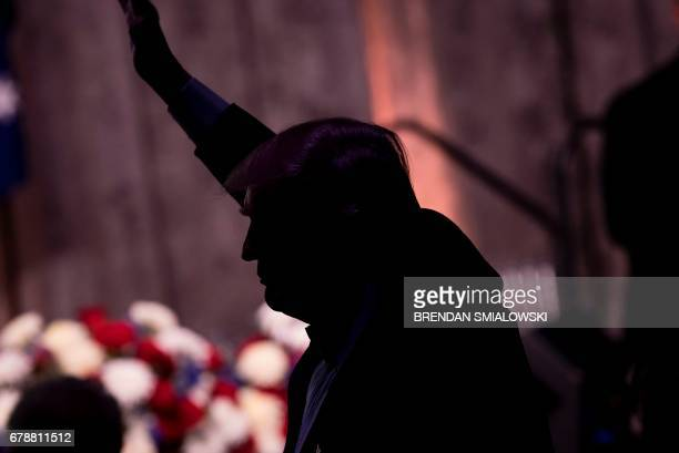 US President Donald Trump waves during a dinner to commemorate the 75th anniversary of the Battle of the Coral Sea during WWII on board the Intrepid...