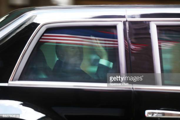 S President Donald Trump waves from his motorcade vehicle after departing Trump Tower on August 16 2017 in New York City Trump is traveling to...