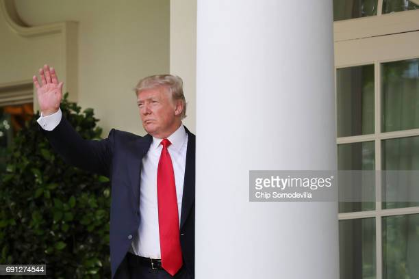 President Donald Trump waves goodbye after announcing his decision to pull the United States out of the Paris climate agreement in the Rose Garden at...