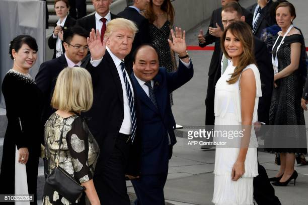 US President Donald Trump waves next to Vietnam's Prime Minister Nguyen Xuan Phuc and US First Lady Melania Trump prior to a concert at the...