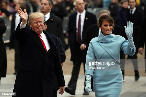 S President Donald Trump waves to supporters as he walks the parade route with first lady Melania Trump during the Inaugural Parade on January 20...