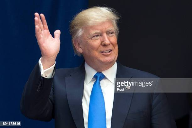 President Donald Trump waves to the audience before delivering remarks on infrastructure investment and deregulation at the Department of...