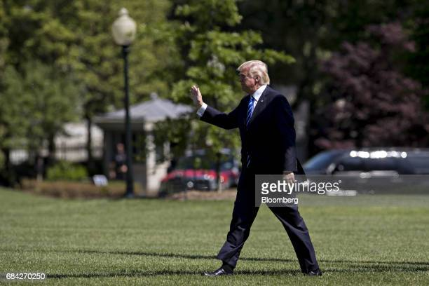 US President Donald Trump waves to visitors as he walks on the South Lawn towards the White House after arriving on Marine One in Washington DC US on...