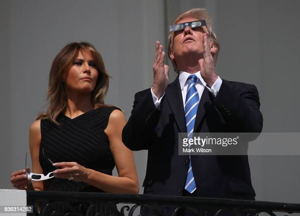 US President Donald Trump wears special glasses as he looks up toward the Solar Eclipse while standing with his wife first lady Melania Trump on the...