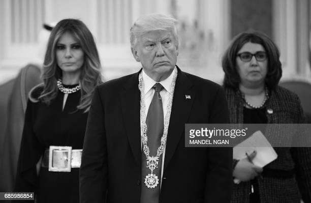 US President Donald Trump wears the Order of Abdulaziz alSaud medal watched by First Lady Melania Trump and a translator after receiving it from...