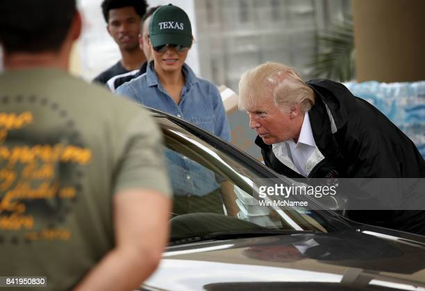 S President Donald Trump with First Lady Melania Trump behind talks with a resident of the Pearland Texas area after helping to load emergency...