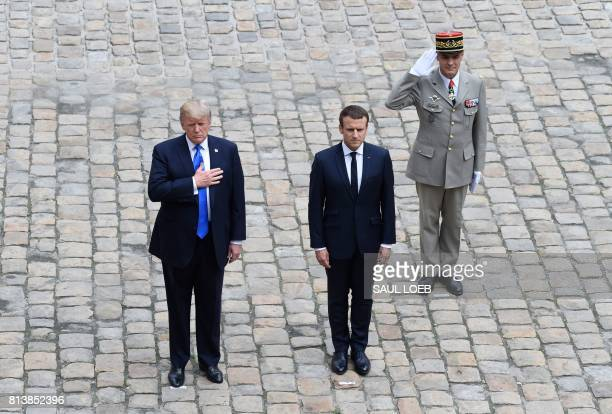 US President Donald Trump with his hand on his heart French President Emmanuel Macron and Military governor of Paris and French army general Bruno Le...