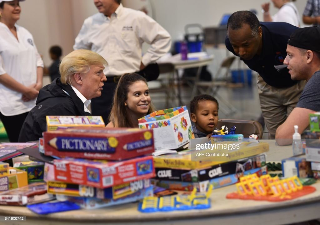 US President Donald Trump, with Secretary of Housing and Urban Development Ben Carson (2nd R), visits Hurricane Harvey victims at NRG Center in Houston on September 2, 2017. US President Donald Trump, with visits Hurricane Harvey victims at NRG Center in Houston on September 2, 2017. / AFP PHOTO / Nicholas Kamm