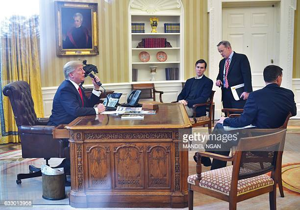 US President Donald Trumpseen through an Oval Office window gives a thumbs up as he speaks on the phone to King Salman of Saudi Arabia in the Oval...