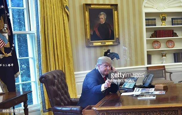 US President Donald Trumpseen through an Oval Office window speaks on the phone to King Salman of Saudi Arabia in the Oval Office of the White House...