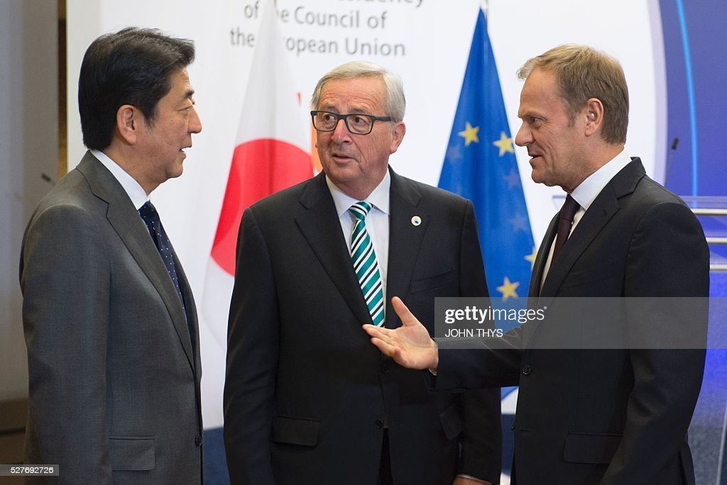 EU President Donald Tusk (R) and European Commission chief Jean-Claude Juncker (C) welcome Japanese Prime minister Shinzo Abe prior to their talks at the EU headquarters in Brussels on May 3, 2016. / AFP / JOHN