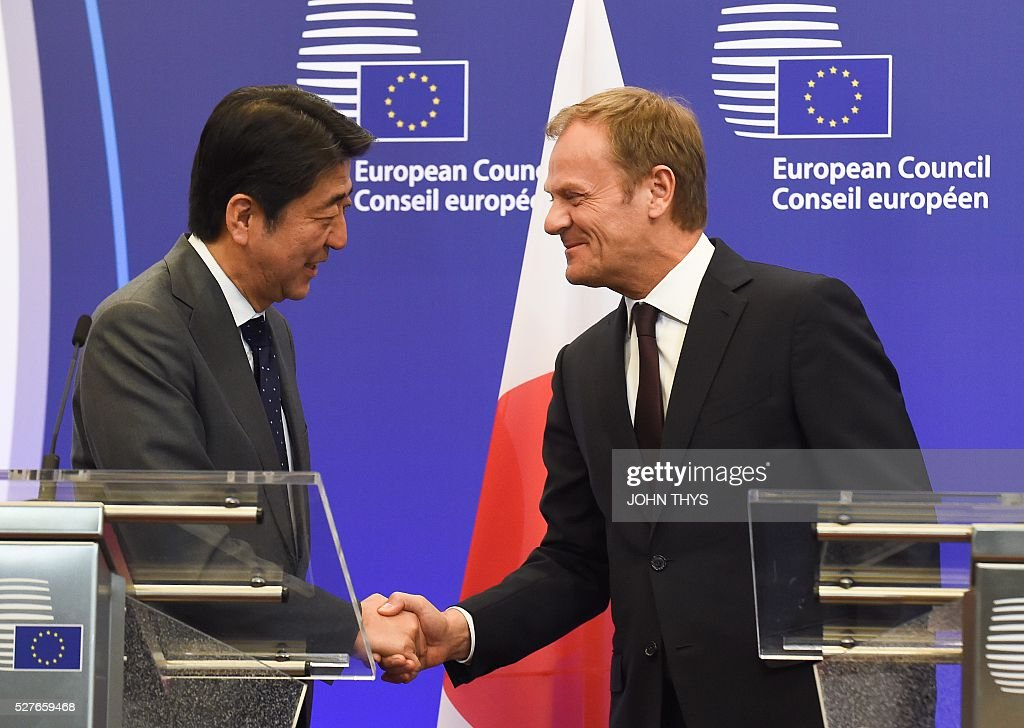 EU President Donald Tusk (R) shakes hand with Japanese Prime Minister Shinzo Abe prior to their meeting at the EU headquarters in Brussels on May 3, 2016. Japanese Prime Minister Shinzo Abe was holding talks in Brussels on May 3 with EU President Donald Tusk and European Commission chief Jean-Claude Juncker. / AFP / JOHN