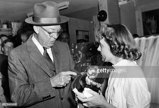 US president Dwight Eisenhower buys a doll in a shop for his little girl on the fringe of the Conference in Geneva on July 20 1955 / AFP / ATP /