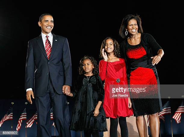 S President elect Barack Obama stands on stage along with his wife Michelle and daughters Malia and Sasha during an election night gathering in Grant...