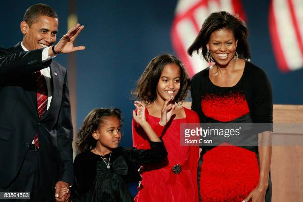 S President elect Barack Obama walks on stage with his wife Michelle and daughters Malia and Sasha to address his supports during an election night...
