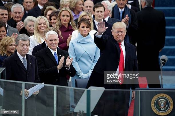 President Elect Donald Trump waves to spectators as Vice President Elect Mike Pence and Melania Trump look on at the West Front of the US Capitol on...