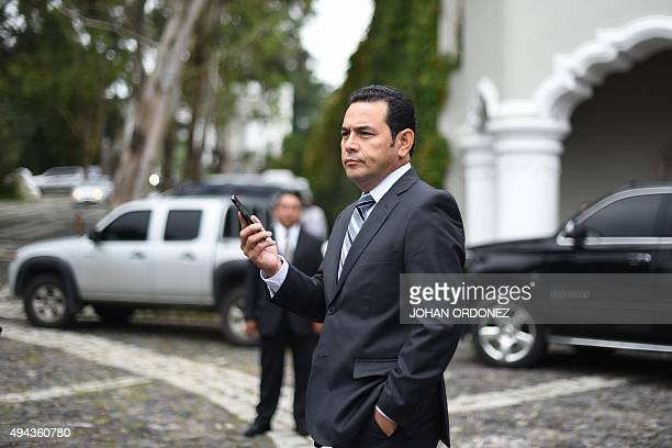 President elect Jimmy Morales of the National Front Convergence speaks by mobile after a press conference in Guatemala city on October 26 2015...