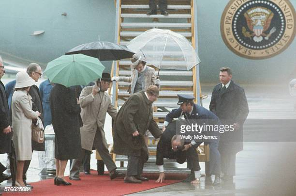 President Ford is helped to his feet after he slipped and fell as he was deplaning Air Force One