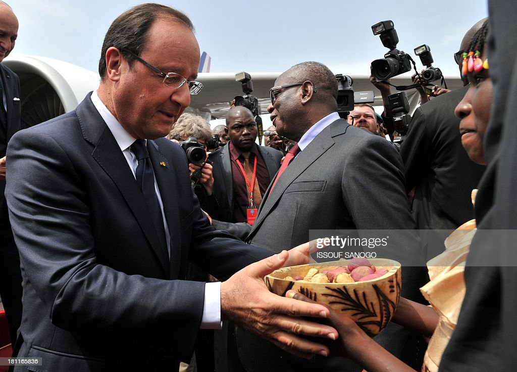 President Francois Hollande of France (L) receives cola nut from a young girl as he is greeted by his Malian counterpart Ibrahim Boubacar Keita (Center R) on September 19, 2013, at the Bamako airport. Leaders from across Africa and France watched the inauguration of Mali President Ibrahim Boubacar Keita in front of thousands of his supporters today as the nation entered a new era of democracy after months of political chaos.