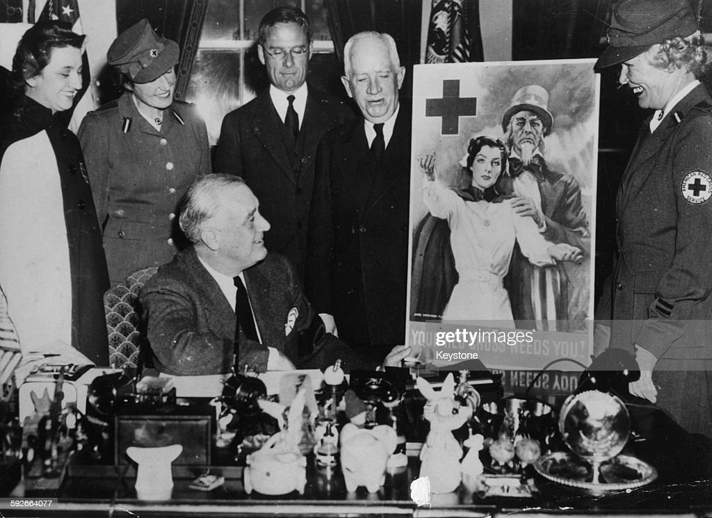 President Franklin D Roosevelt is presented with the new American Red Cross poster by members of the organization at the inauguration of the Red...