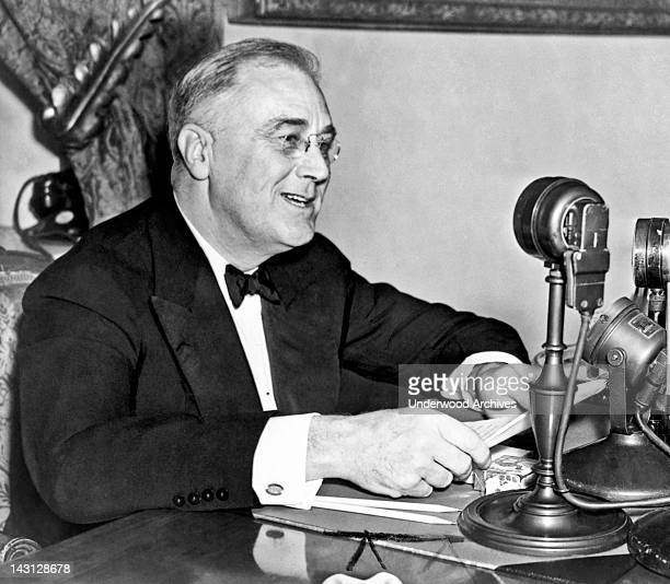 President Franklin D Roosevelt seated behind microphone during one of his fireside chats Washington DC 1937